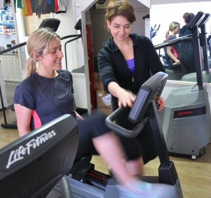 A Female Personal Trainer Helping A Woman On A Machine In The Gym