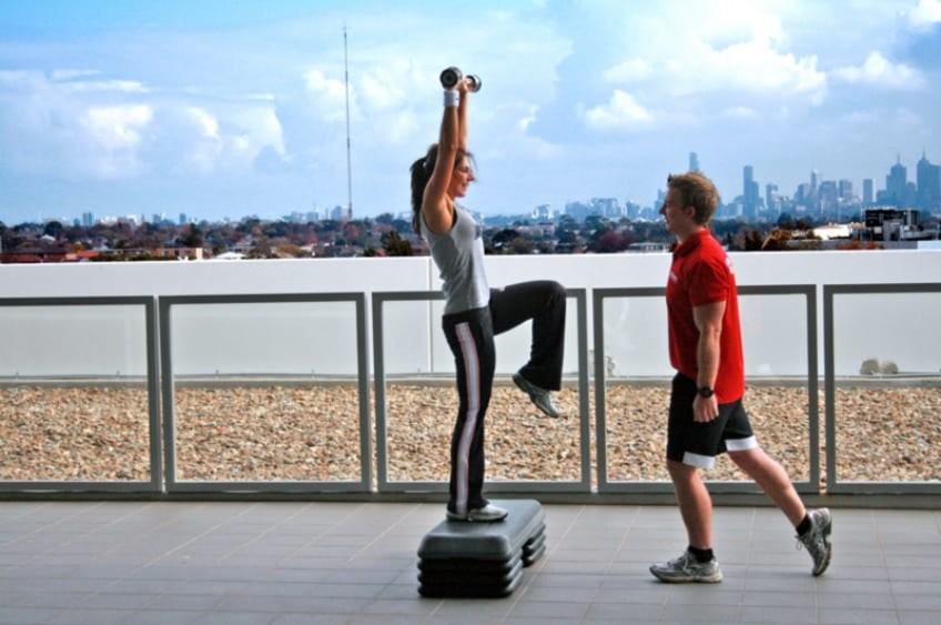 A Personal Trainer Helping A Woman Workout By The River In Melbourne